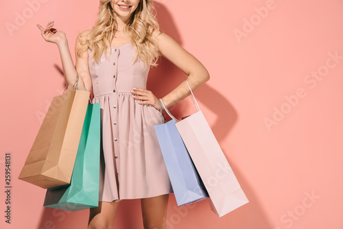 Leinwandbild Motiv cropped view of blonde woman with shopping bags on pink background
