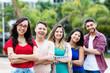 Leinwandbild Motiv Junge Frau mit Brille und anderen Jugendlichen in Reihe