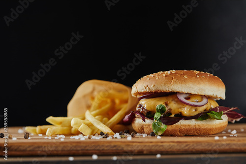 salt, french fries and delicious burger with meat on wooden surface isolated on black - 259558965