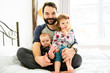 A Nice father with kids on bed