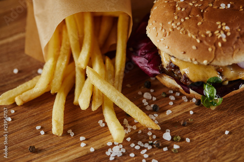 Leinwandbild Motiv salt, french fries and delicious burger with meat on wooden surface