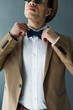 partial view of stylish mixed race man in suit adjusting bow tie isolated on grey