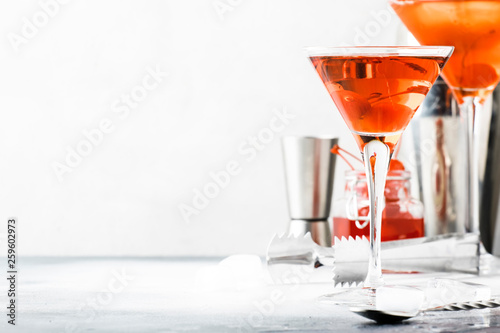 Leinwandbild Motiv Classic alcoholic cocktail Manhattan with american bourbon, red vermouth, bitter, ice and cocktail cherry in glass, tools, gray bar counter background, copy space, selective focus