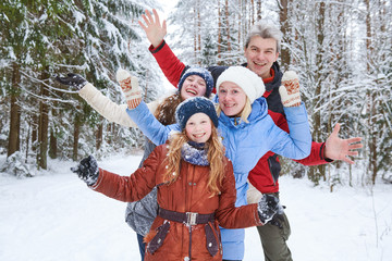 happy smiling family in winter snowy forest