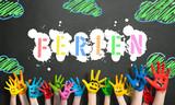 angemalte Kinderhände vor Kreidetafel mit dem Wort