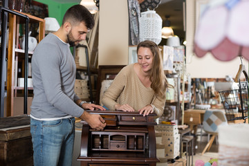 Man with girlfriend admiring vintage wooden bureau