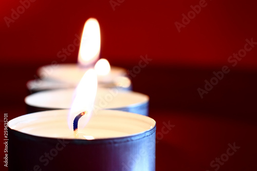 Close up of a burning wax candle against a red background © Andrew Gardner
