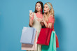 Quadro surprised brunette and blonde women in dresses holding shopping bags and using smartphone