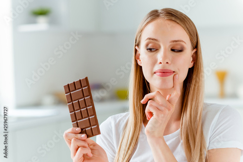 Leinwanddruck Bild Close-up portrait of her she nice-looking cute charming lovely attractive cheerful girlish foxy straight-haired girl wearing white tshirt looking at choco bar in light white interior room