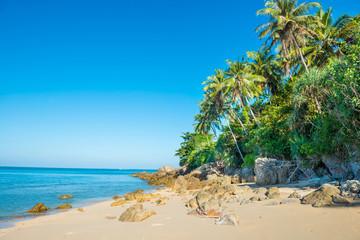 Tropical beach with rocks, palm trees, blue sea and white sand