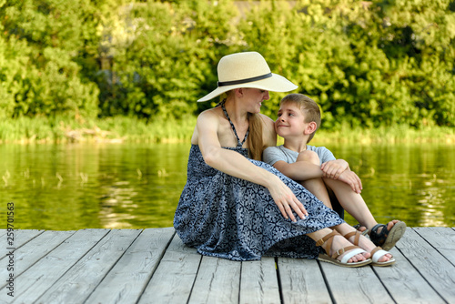 Happy family, young mother with her little son are sitting on the pier by the river © somemeans