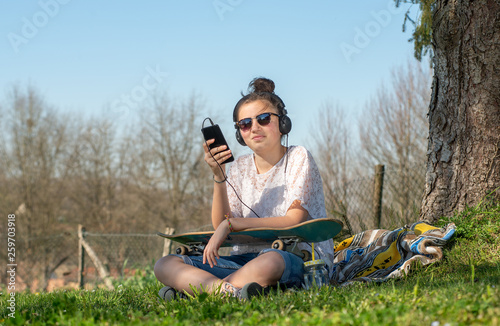 young teenager girl with sunglasses listening music in the park - 259703918