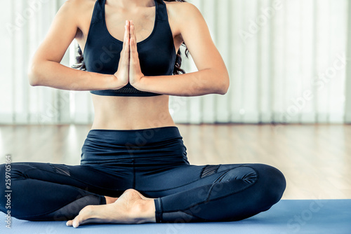 Leinwanddruck Bild Young woman practicing yoga position in an indoor gym studio. Healthy and wellness lifestyle concept.