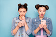 Leinwandbild Motiv Portrait of cute surprised fellows fellowship worried confused impressed by incredible news on gadgets social networks apps screaming omg wow wearing denim jackets isolated on pastel background