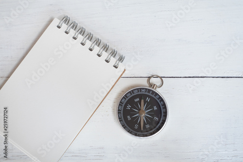 Compass and brown notebook on white wooden table background, journey planning concept