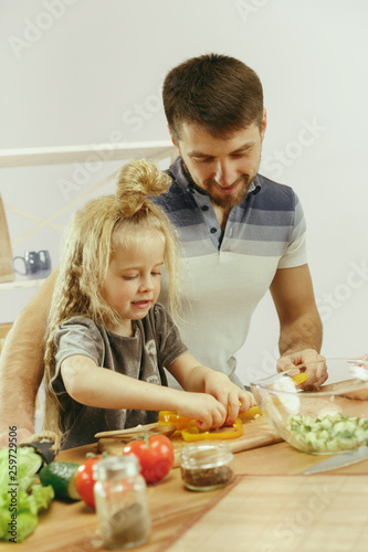 Cute little girl and her beautiful parents are cutting vegetables and smiling while making salad in kitchen at home. Family lifestyle concept - 259729506
