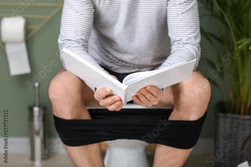 Leinwandbild Motiv Man reading book while sitting on toilet bowl at home