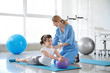 Physiotherapist working with little girl in rehabilitation center - 259737382