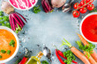Set of various vegetable cream soups, Carrot, beet root, spicy tomato pureed soups with fresh organic veggies, blue concrete background, copy space