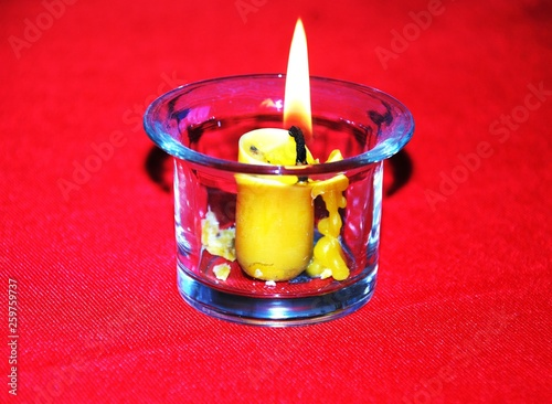 wax candle burning in a glass candlestick, which stands on a red napkin © Aleksandr