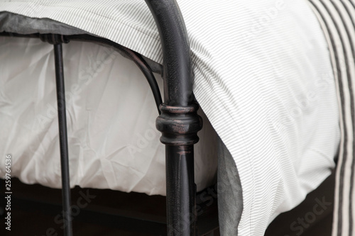 close up of bedding iron frame with white comfortable blanket and mattress © bennnn
