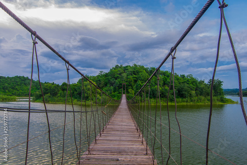 Suspension bridge across to the island on a cloudy day - 259772784