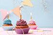 Delicious cupcakes with candles on a colored background. Festive background, birthday