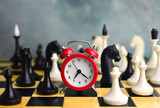 Time management in business. Concept with clock on chess board.