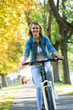 Young woman ride bike in autumn park. Enjoying while cycling in nature during autumn day.