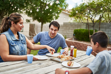 happy hispanic family eating grilled hot dogs on picnic table in backyard