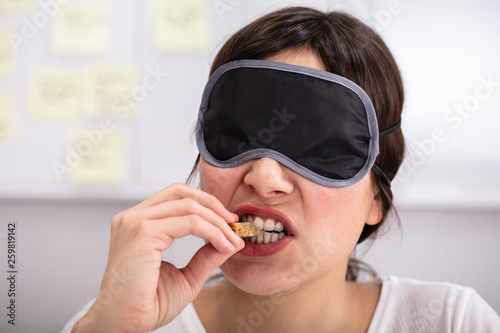 Leinwandbild Motiv Blindfolded Young Woman Testing Food