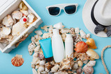 summer skin care cosmetics, panama and sunglasses on blue background.  bottles of woman cosmetics on seashells. Summer holidays or vacation. Preparation for summer care. Sunscreen protection products - 259822737