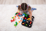 Girl Sitting On Carpet Playing With Colorful Blocks