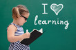 Girl In Front Of Chalkboard With I Love Learning Text - 259825751