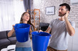 Quadro Couple Using Bucket For Collecting Water Leakage From Ceiling