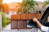 Woman in car, hand using remote control to open auto wooden door with modern home blurred background. Automatic gate concept.