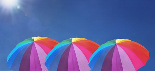 three rainbow umbrella in line under sunny blue sky