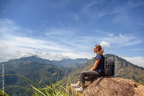 Happy young beautiful girl tourist with a backpack. Sit in the mountains and enjoy the view and nature. - 259856751