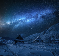 Small cottages in winter mountains and milky way