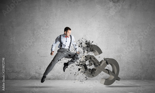 canvas print picture Determined banker man in empty concrete room breaking dollar figure