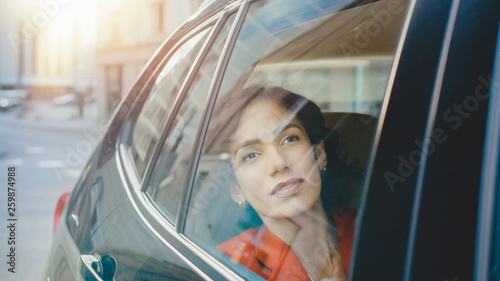 Beautiful Sad Woman Rides on a Passenger Back Seat of a Car, Looks out of the Window Dreamily. Big City View Reflects in the Window. Camera Mounted outside Moving Car.