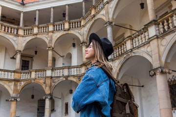 Young woman in hat and denim jacket with backpack in old castle