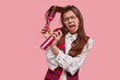 Leinwandbild Motiv Woman in panic has problematic hair, can not brush, has depressed facial expression, holds hairbrush and hairspray, late for date, dressed in old fashionable clothes, isolated on pink background