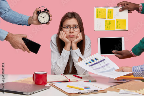 Leinwanddruck Bild Sad female workaholic keeps hands under chin, busy making project work, studies papers, wears elegant white shirt, sits at desktop, unknown people stretch hands with notes, alarm clock, smartphone
