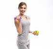 Sporty fit woman holding dumbbells weights in one and apple fruit in another hand. Fitness and healthy dieting concept.