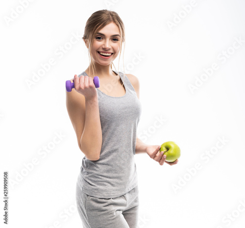 Sporty fit woman holding dumbbells weights in one and apple fruit in another hand. Fitness and healthy dieting concept. © opolja