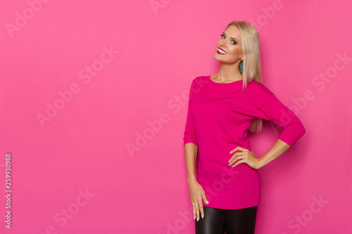 Beautiful Blond Woman In Pink Sweater Is Holding Hand On Hip And Looking At Camera - 259930988