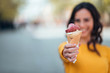 Girl holding ice cream cone toward camera outdoors, focus on the foreground, copy space.