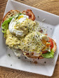 Egg Benedict with ham and salad on a toast bread