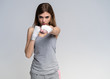 Beautiful boxer girl wearing sportive clothing and gloves practicing in the studio over gray background, athletic body, healthy lifestyle.